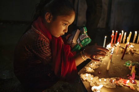 A young girl lights candles at a Kabul temple during the annual Diwali celebration