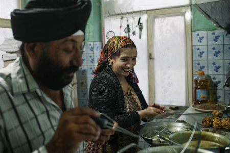 Rawail Singh, one of the leaders of Kabul's Sikh community, helps his wife with cooking before the Diwali festival