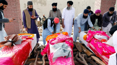 Afghan Sikh men prepare coffins after a deadly attack at a Sikh religious complex in Kabul on Mar. 25, 2020