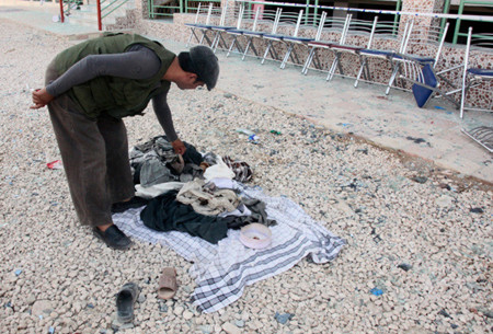 A man searches clothes of victims at the site of attack in Samangan province