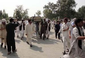 Afghan men carry the bodies of those killed in a coalition air strike on 14 July, 2011
