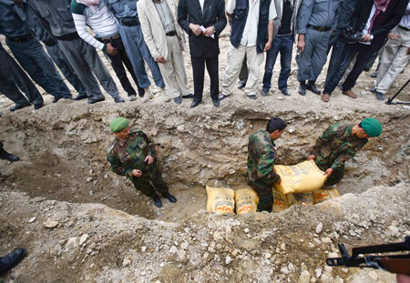 Afghan soldiers prepare to dispose of bags of ammonium nitrate used in roadside bombs