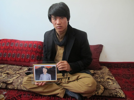 Esmail Kayhan, an ethnic Hazara, holds a portrait of his father, Mohammad Jomah Amini, who was among the 31 men and boys kidnapped in Zabul province