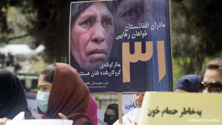 Placard showing a mourning mother of a hostage held by Taliban in a protest by the Solidarity Party of Afghanistan
