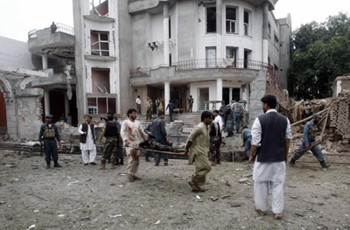 Remains of a dead body are carried away from the site of a suicide attack in Jalalabad province