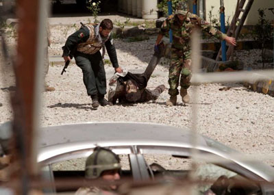 An Afghan Army solider and policeman drag the lifeless body of a suicide bomber