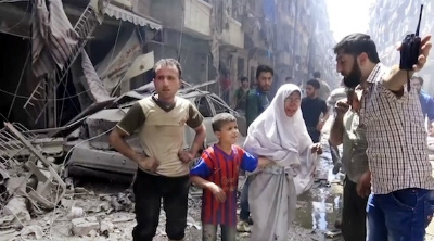 A man leads a tearful woman and a child out of the area after airstrikes hit Aleppo, Syria