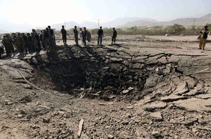Afghan police officers gathered near a crater left after a vehicle packed with explosives detonated outside of the Afghan intelligence headquarters in Maydan Shahr, the capital of Wardak Province