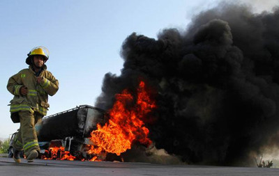 An Afghan firefighter run next to a burning oil tanker carrying fuel supplies for NATO forces after it was allegedly attacked by Taliban on Jalalabad highway, east of Kabul