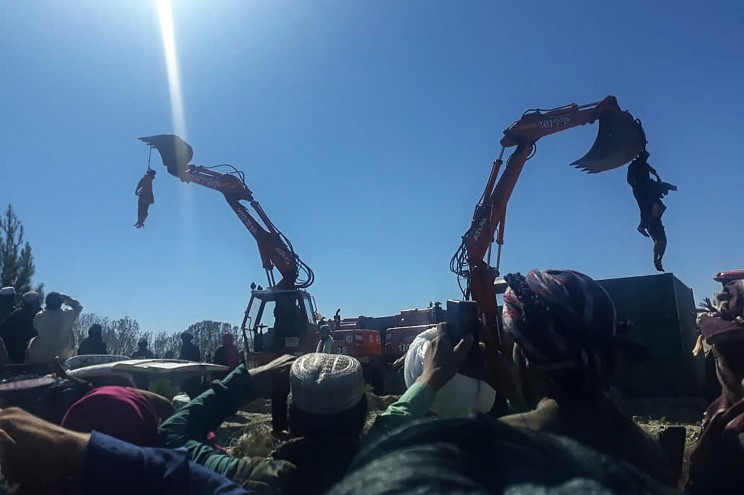 the bodies of three alleged criminals are hung from two cranes in a public