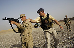 Brian Martin, Ex-Marine and US mentor of Afghan National Police (ANP), instructs a student during the fire arms component of tactical training program