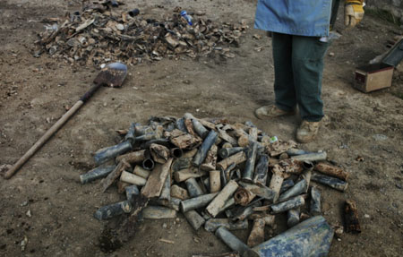 A man separates metal from old artillery shells at Bagram air base