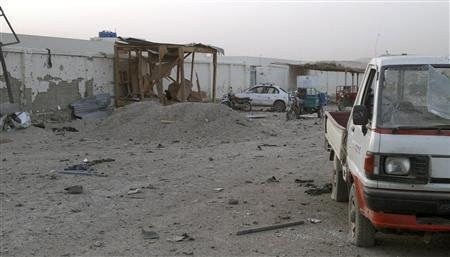 Damaged vehicles are seen inside the government compound in Uruzgan province July 28, 2011