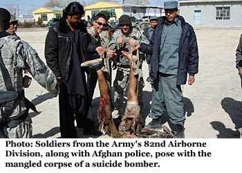 Soldiers from the army's 82nd Airborne Division, along  with Afghan police, pose with the mangled corpse of a suicide bomber.
