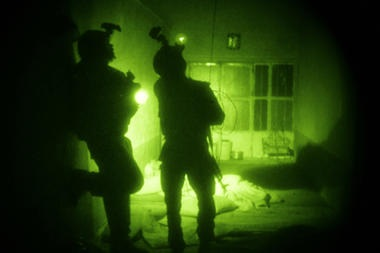In this 2009 file photo taken with a night vision scope, U.S. Special Operations forces search a home during a joint operation with Afghan National Army soldiers targeting insurgents operating in Afghanistan's Farah province