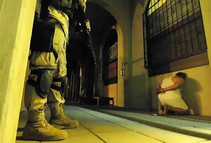 A US soldier guards a detained suspected Iraqi insurgent during a night raid in Baghdad