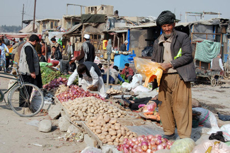 A vegetable seller stands over his goods in a Kabul neighborhood where 50 people from just 15 families were killed or injured when a suicide bomber killed more than 80 people