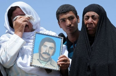 Afghan woman with portrait of her dead husband