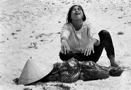 A South Vietnamese woman mourns over the body of her husband, found with 47 others in a mass grave near Hue in April 1969