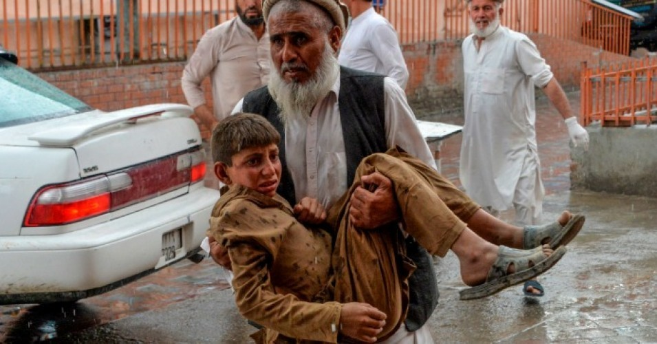 A volunteer carries an injured youth to a hospital