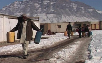 Afghan IDPs carrying water to their camp