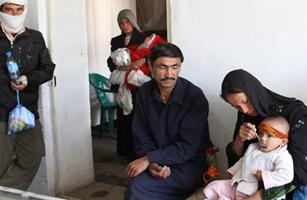 Salamudin, 36, center, waits at a pharmacy in the Afghan town of Bamiyan with his wife Bakhtawar, 22, and their 1-year-old son Surodin
