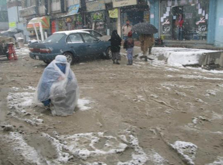 Poor woman begging in snowfall