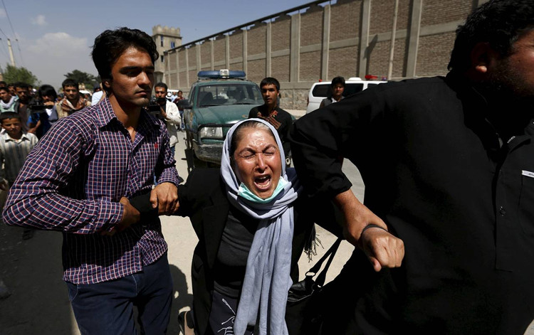 A woman reacts as she looks for her relatives at the site of the Kabul attack, which the Taliban claimed responsibility