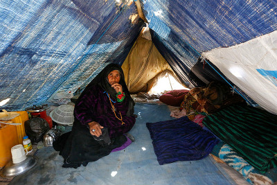 Internally displaced woman in her temporary shelter in an informal settlement on the outskirts of Herat city
