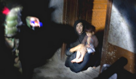 A woman with her child in the Afghan village of Darbart cowered in a doorway during a night raid in April 2009