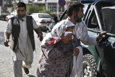 Afghan men rush a wounded woman to receive treatment, after a suicide car bomber struck outside the Afghan Supreme Court in Kabul