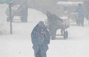 A woman struggles to make her way through the snow covered streets of Kabul as the snow keeps falling