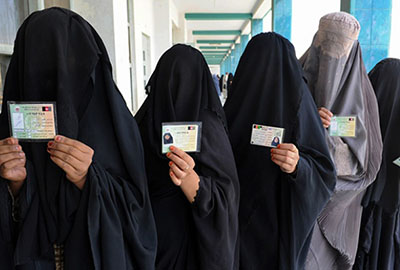 Afghan women show identification cards as they wait to cast their votes in Afghanistan