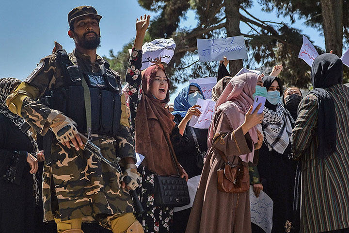A Taliban fighter stands guard as Afghan women shout slogans during an anti-Pakistan protest rally