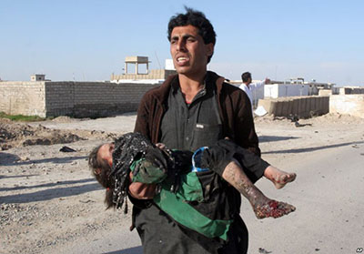 An Afghan man carries a wounded girl at the side of a suicide attack that killed civilians and a policeman in Lashkar Gah, the capital of Helmand province, south of Kabul, Afghanistan, March 16, 2015.