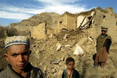 Afghan villagers stand in front of one of the houses bombed by a US NATO air strike on Jabar village in the Nijrab district of Kapisa province