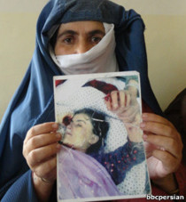 Rape victim's mother holds photo of her dead daughter.