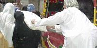 RAWA distributes flour and ghee among refugees in Akora Khattak Camp